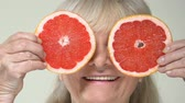 toranja : Happy mature female holding grapefruit slices front of eyes, vitamins nutrition