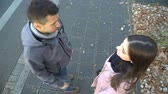 ököl : Young couple arguing on street, man leaving his girlfriend alone, going away