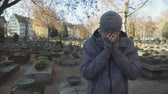 относительный : Man standing on cemetery and deeply crying, missing lost family, loneliness Стоковые видеозаписи