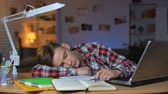 disziplin : Extremely tired student sleeping by table on pile of books, overloaded pupil