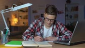disiplin : Diligent teen student in glasses finishes homework and looks directly to camera Stok Video