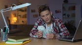 сумма : Teenage boy counting dollar bills thinking about new purchase, dreaming