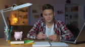 disiplin : Teenager holding euro banknote putting it to piggyback, financial education Stok Video