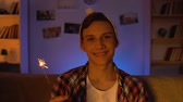 сочельник : Funny teenager holding bengal lights smiling to camera, alone on Christmas