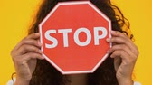 racismo : Biracial girl holding stop sign, protesting bullying or racism, gun violence Archivo de Video