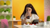 gastritis : Female cafe customer biting tasteless burger drinking soda water, cheap food Stock Footage