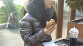 indifferent : Happy young woman eating sandwich cafe and looking at homeless outside, society