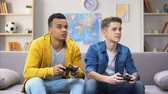 dormitory : African and European teenager friends losing video game, accusing each other