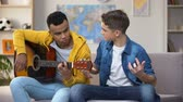 harcamak : African-American teenager teaching Caucasian friend to play guitar, hobby