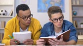 coletivo : Multiracial students interested with information written in book preparing Vídeos