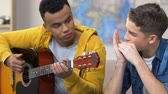 principiante : Two teenagers playing guitar and harmonica, musical hobby, amateur musicians