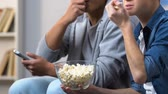 suspens : Two male friends eating popcorn in front of tv watching drama series episode