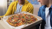 dorm : Two male students opening pizza box and looking at tasty caloried meal, fastfood