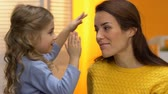 dolcezza : Cute preschool girl closing smiling mothers eyes with hands, happy family moment