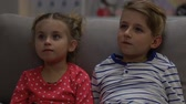 Boy and girl watching tv at night, scared when parents suddenly return home