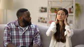 раздраженный : Young lady closing ears with hands, ignoring her black boyfriend talk, quarrel