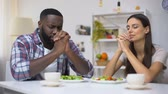 požehnaný : Young mixed-race couple praying before lunch, vegetarian healthy salad on table