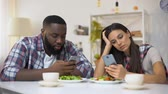família : Offended mixed-race couple using smartphones during lunch, misunderstanding