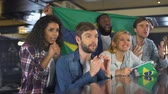 derrota : Sport fans waving Brazil flag, supporting national team, upset about defeat Stock Footage