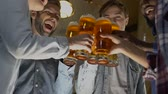 supporting : Happy group of friends clinking beer glasses, birthday party celebration in pub