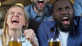 野球 : Young friends celebrating favorite sports team goal clinking beer glasses in pub