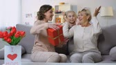 carte d amour : Female grandchild covering granny eyes presenting surprise gift, mothers day