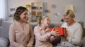 receber : Pretty woman with daughter presenting nice gift box to grandmother, birthday