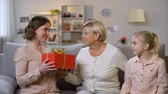 recibiendo : Elderly woman with granddaughter presenting gift box mother, holiday tradition