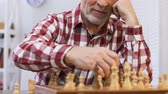 pensão : Smiling mature man making chess move and looking into camera, pension reform