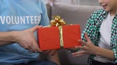 doação : Volunteer presenting giftbox to little boy from low-income family, state support