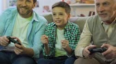 podporující : Father and grandpa playing video game at home, boy cheering for victory, relax