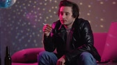 nikotin : Relaxed male smoking cigarette, chilling out at private disco party, leisure