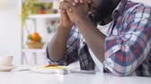 doba jídla : African american man praying before eating, asking god to bless food, faith
