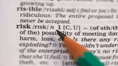 explicando : Risk, pencil pointing word in english dictionary, possibility of losing assets Stock Footage