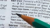 terrorismo : Terrorism word pointed in dictionary, supporting violence, using aggression Stock Footage