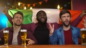 extremely : Italian soccer team losing game, multiracial male friends disappointed, pub