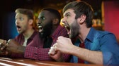 bosse : Cheerful multiracial friends celebrating team victory, giving fist bump, race