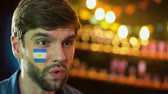 resultados : Argentinian football fan with flag on cheek making facepalm, unhappy with loss Archivo de Video