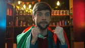 Результаты : Nervous sports fan with Portuguese flag watching match in pub upset about defeat