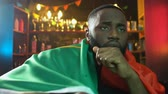 vlag portugal : Sad black fan holding flag of Portugal in bar, upset about sports team defeat