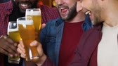 celebração : Multiethnic male friends clinking beer glasses, evening in pub, leisure time