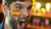 頬 : Spanish football fan with flag on cheek rejoicing favorite team victory, league