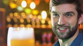 celebração : Smiling Caucasian man clinking beer glass in pub, evening leisure time, relax Stock Footage