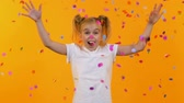 celebração : Little excited girl smiling standing under confetti rain on orange background