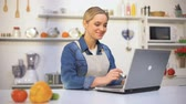 kitchen device : Positive beautiful girl searching cooking tips in internet, novice in kitchen