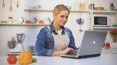 tipp : Young pretty woman in apron searching food recipe instructions in internet blog Stock mozgókép