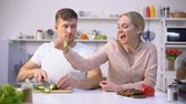 nourishment : Happy couple flirting, cooking salad of fresh vegetables, healthy gmo free food