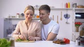 nourishment : Romantic couple cooking salad, lovingly embracing, happy healthy vegan lifestyle