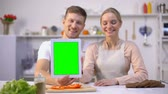kitchen device : Couple holding tablet with green screen, showing thumbs up, delicious recipe app