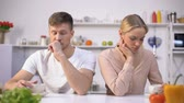 casamento : Young couple sitting silently in kitchen after argument, crisis in relationship